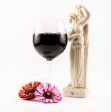 Composition of black wine, flowers and an elegant Renaissance statue on a white background Royalty Free Stock Photos