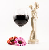 Composition of black wine, flowers and an elegant Renaissance statue on a white background Royalty Free Stock Images