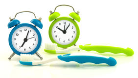 Composition from blue and green clocks and toothbrushes Royalty Free Stock Image