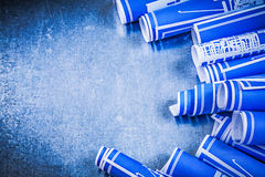 Composition of blue rolled construction drawings on metallic bac Stock Photo