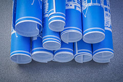 Composition of blue rolled up construction drawings on grey back Royalty Free Stock Images