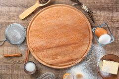 Composition with board and some products. For cooking vanilla cake on wooden background stock image