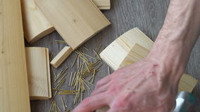 Composition of boards, nails and hammer,hand hammer puts in the frame stock video footage