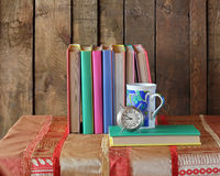 Composition with books. Back to school. Composition with books, an alarm clock and a glass with a blue pattern on a table with a red cloth. Back to school Royalty Free Stock Photos