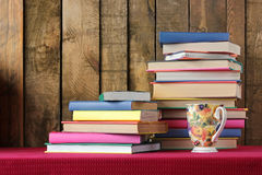 Composition with books and a glass. Back to school. Composition with books and a glass on a table with a red cloth. Back to school Stock Image