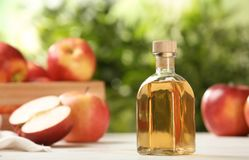 Composition with bottle of apple vinegar on table. Space for text stock image