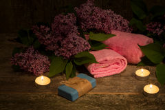 Composition with a bouquet of lilacs and candles on the old wood Stock Photo