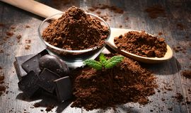 Composition with bowl of cocoa powder on wooden table Royalty Free Stock Images