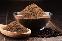 Composition with bowl of ground black pepper on wooden table Royalty Free Stock Photo