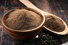 Composition with bowl of ground black pepper on wooden table Stock Photo