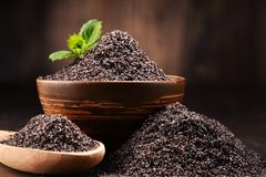 Composition with bowl of poppy seeds on wooden table Royalty Free Stock Image