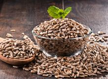 Composition with bowl of shelled sunflower seeds on wooden table Stock Images