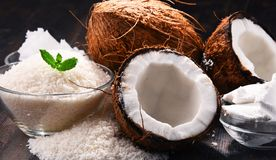 Composition with bowl of shredded coconut and shells. On wooden table Royalty Free Stock Image