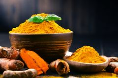 Composition with bowl of turmeric powder on wooden table.  royalty free stock image