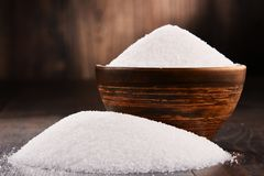 Composition with bowl of white refined sugar on wooden table Stock Photo