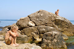 Composition of boy n girl sitting on rocks. Composition of boy and girl sitting on rocks next to sea. Shot in the Cape Aia Nature Reserve, near Balaklava/ Stock Photo