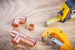 Composition of brass pipe cutter fittings measuring tape on wood Royalty Free Stock Photo
