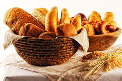 Composition with bread and rolls in wicker basket, combination of pastries for bakery or market with wheat Royalty Free Stock Images