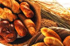 Composition with bread and rolls in wicker basket, combination of pastries for bakery or market with wheat Stock Photo
