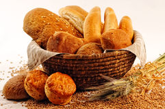 Composition with bread and rolls in wicker basket, combination of pastries for bakery or market with wheat Royalty Free Stock Photos