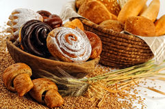 Composition with bread and rolls in wicker basket, combination of sweet pastries for bakery or market with wheat Royalty Free Stock Photo