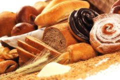 Composition with bread and rolls in wicker basket, combination of sweet pastries for bakery or market with wheat Stock Image