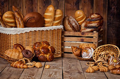 Composition with bread and rolls in wicker basket. Isolated over dark background Royalty Free Stock Image