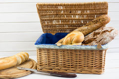 Composition with bread and rolls in wicker basket  on white background. Royalty Free Stock Images