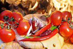 Composition with Bread, Tomatoes, Hot Chili Pepper and Garlic. Bread, tomatoes,  Chili Pepper and garlic on the background of coals Stock Photo