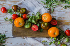 Composition of bright tomatoes on wooden background. Flatlay. Top view. Royalty Free Stock Photos