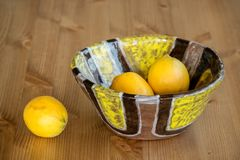 Composition of bright ceramic bowl and yellow lemons. Royalty Free Stock Image
