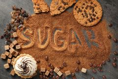 Composition with brown sugar and variety of sweets. On grey background stock images