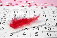 Composition with calendar, menstrual pad. And feather. Gynecological checkup stock photo