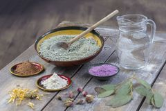 Composition of ceramic bowls of sea clay powder: red, pink, green ,purple ,pitcher of water, dryflowers, eucaliptus Royalty Free Stock Photo