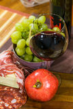 Composition of cheese, bacon, pomegranate, glass of wine and yellow muscat grape on a wooden board Stock Photography
