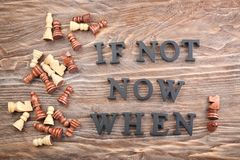 Composition with chess and phrase Is not now. When? composed from letters on wooden table. Time management concept royalty free stock images