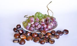 Autumn fruits, chestnuts and grapes. Composition with chestnuts and grapes, dried leaves, white background Royalty Free Stock Photography