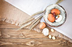 Composition of chicken and quail eggs on burlap and wooden boards. With ears of wheat Stock Image