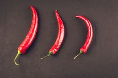 Composition of chili pepper/red hot Chile pepper on a dark stone background. Top view stock image