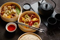 Composition of chinese food. Mixed kinds of dumplings from wooden bamboo steamer stock photo