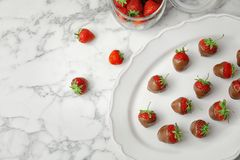 Composition with chocolate covered strawberries on marble background. Flat lay composition with chocolate covered strawberries on marble background stock photo