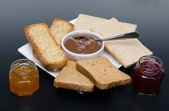 Composition of chocolate hazelnut spread, jams and different rus Royalty Free Stock Images