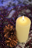 Composition of a Christmas candle, cones and beads Royalty Free Stock Photos