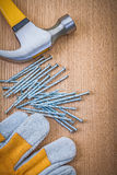 Composition of claw hammer nails and protective glove on wooden Royalty Free Stock Photography