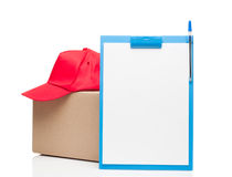 Composition with clipboard red cap and cardboard box Royalty Free Stock Images