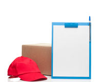 Composition with clipboard red cap and cardboard box. On white Royalty Free Stock Photography
