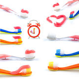 Composition from clock, color toothbrushes with toothpaste, set Stock Image