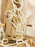 Composition with clothespins, cord and vase. Against beige textile background Stock Photography