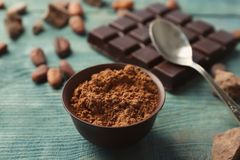 Composition with cocoa powder and chocolate bar. On wooden background Stock Image