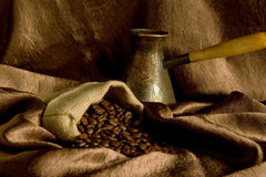 Composition with coffee beans. Coffee beans in a bag and cezve on a brown background Royalty Free Stock Images